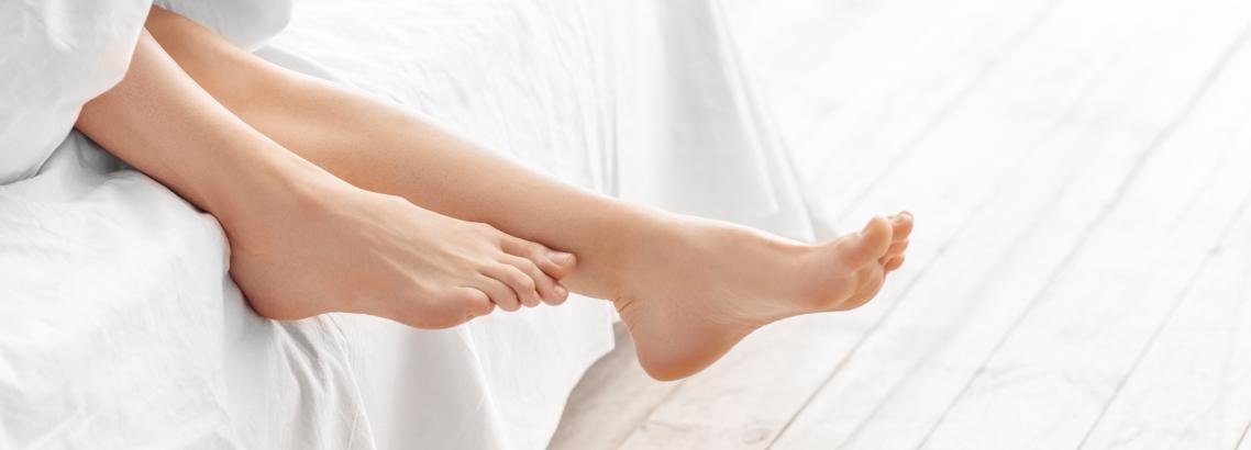 Picioare care ies din pat de sub pătură